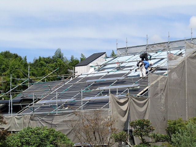 カバー工法 職人さんが屋根の上で施工しています